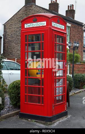 Defibrillator in red phone box, england - Stock Photo
