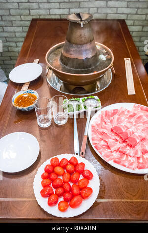 A traditional Chinese hotpot with meat and condiments. - Stock Photo