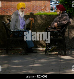 two elderly sikh man wearing yellow and red turbans sitting opposite each other on public benches Southall london - Stock Photo
