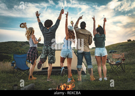 Happy young friends enjoy a nice day in nature. They're looking at sunset and greeting, happy to be together. - Stock Photo