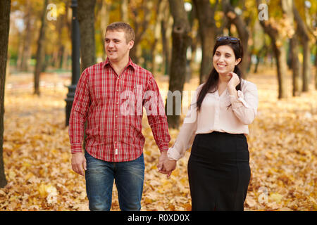Couple is walking in autumn city park. Bright yellow trees. - Stock Photo