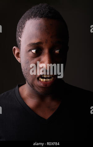 Studio shot of angry young black African man screaming in dark r - Stock Photo