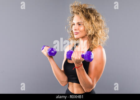 Photo of slim sporty woman doing exercises with small dumbbells isolated over gray background - Stock Photo