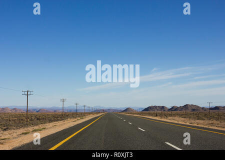 long empty tarred national road stretches out into the distance in a dry and arid landscape of South Africa on the Cape Namibia route - Stock Photo