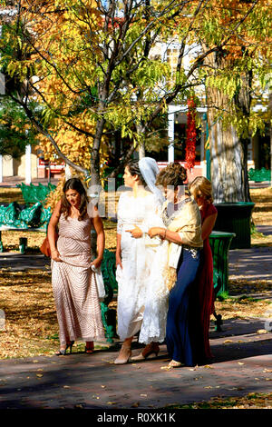 Woman in her wedding surrounded by her attendants in the Santa Fe Plaza in downtown Santa Fe, New Mexico USA - Stock Photo