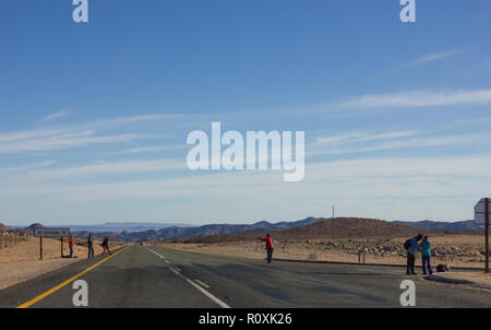 Pedestrians and hitch hikers standing on the N7 road which leads to Namibia from South Africa - Stock Photo