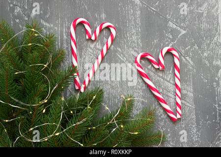 Winter background with fir branches, garland and candy canes on a gray concrete background. Greeting card, selective focus. - Stock Photo