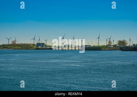 Panoramic view of onshore horizontal axis wind turbines generating electricity at the coast of the Baltic Sea in Germany on a nice day with a blue sky. - Stock Photo