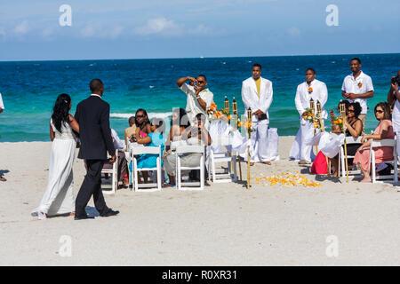 Miami Beach Florida Atlantic Ocean public beach seashore destination wedding ceremony Black man woman couple guest groom bride m - Stock Photo