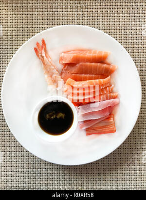 Japanese Food, seafood sashimi: fresh sweet shrimp, raw sliced salmon, tuna and crab meat with soybean sauce and green horseradish in white plate on t - Stock Photo