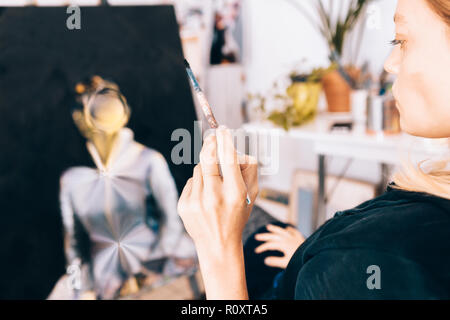 close up of a female artist painter while holding a paintbrush - Stock Photo