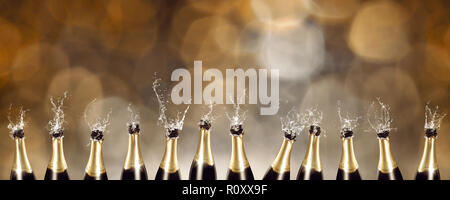 Splashing Champagne bottles with blurred lights in the background - Stock Photo