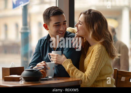 Young attractive couple on date in coffee shop having a conversation and enjoying the time spent with each other. - Stock Photo