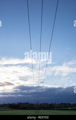 A silhouette of a powerline, with cloudy sky in the field near Swindon Village in Cheltenham, Gloucestershire, United Kingdom. - Stock Photo