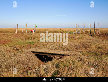 A small wooden footbridge on a path in the salt marshes near the quay in the North Norfolk harbour at Thornham, Norfolk, England, UK, Europe. - Stock Photo