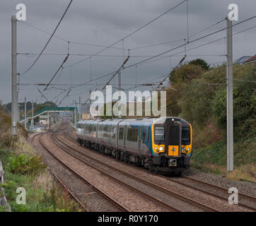 A transpennine Express class 350 electric train passing hest bank on the west coast main line with a Glasgow Central - Manchester Airport train - Stock Photo