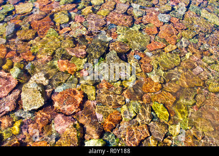 Crystal clear clean shallow water reveals wonderful colours on pebbles underneath the surface.  Beautiful nature being abstract. - Stock Photo