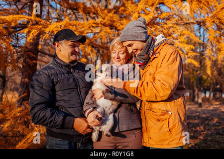 Happy family spending time with pug dog in autumn park. Parents with their son hugging pet. Family values - Stock Photo