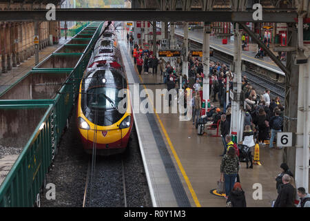A Virgin trains pedolino train arriving at a wet Preston railway station alongside a crowded platform - Stock Photo