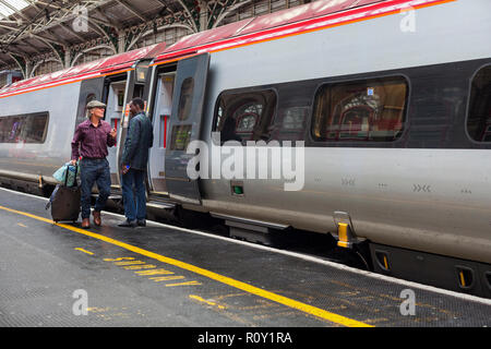 A rail passenger leaving a Virgin trains west coast Pendolino train at Preston railway station, Lancashire - Stock Photo