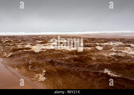 The outflow of Sandwood loch in flood conditions crossing the beach at Sandwood Bay, Sutherland, Scotland, UK, with the water heavily stained by peat. - Stock Photo