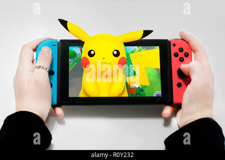 Caucasian girl playing let's go pikachu on a Nintendo Switch gaming console. Pikachu on 3D - Stock Photo