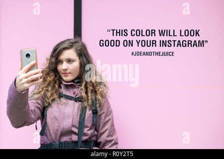 Washington DC, USA - March 9, 2018: Young woman taking selfie against millennial pink color background outside, outdoors in cold winter, dressed in co - Stock Photo