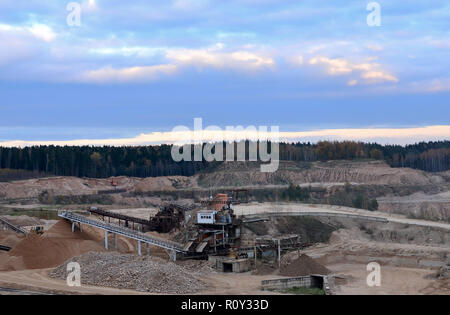 Aerial view of opencast mining quarry with lots of machinery at work - view from above. Production useful minerals. The work of construction equipment - Stock Photo