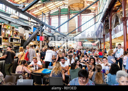 Florence, Italy - August 30, 2018: Interior, inside, indoor of Firenze Centrale Mercato, central market with crowd of people sitting on chairs by tabl - Stock Photo