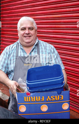 London England United Kingdom Great Britain man mature overweight restaurant kitchen worker apron taking out trash garbage smiling job - Stock Photo
