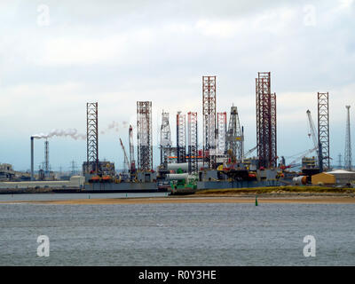 Jack Up drilling rigs at the TERRC Hartlepool  facility on the river Tees for repair and a construction vessel loading offshore windfarm parts - Stock Photo