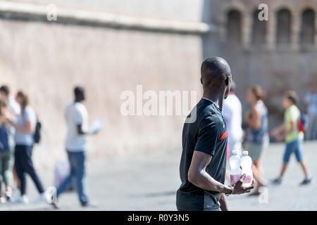 Rome, Italy - September 5, 2018: African black male, man, immigrant, street vendor, seller selling bottled bottles of water, walking road sidewalk wit - Stock Photo
