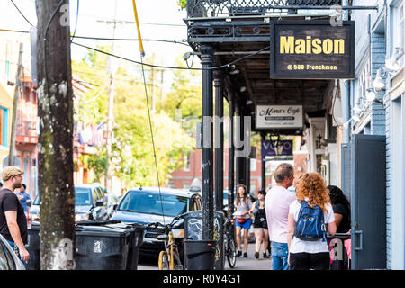 New Orleans, USA - April 22, 2018: Frenchmen street covered sidewalk in Louisiana town, city, building, sign closeup for Maison live music club - Stock Photo