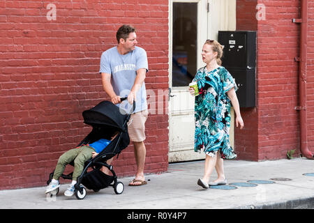 New Orleans, USA - April 22, 2018: Old town street in Louisiana famous city, people tourists couple family talking pushing baby stroller on sidewalk,  - Stock Photo