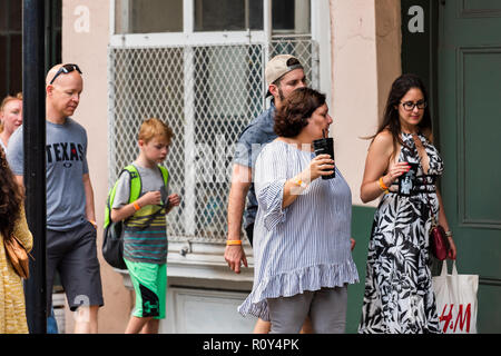 New Orleans, USA - April 22, 2018: Old town street in Louisiana famous city, happy people walking on sidewalk by building wall in evening - Stock Photo
