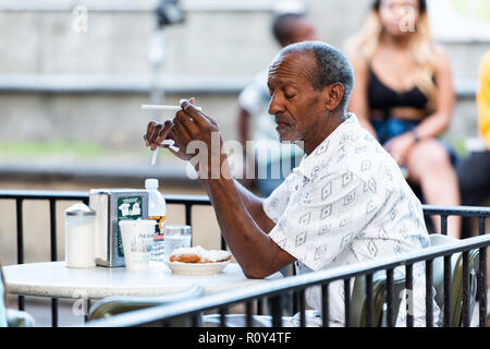 New Orleans, USA - April 22, 2018: Man sitting at table at famous, iconic Cafe Du Monde shop, restaurant eating beignet powdered sugar donuts, coffee, - Stock Photo