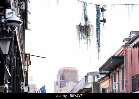 New Orleans, USA Downtown old town Bourbon street in Louisiana famous town, city, mardi gras beads hanging on cable wire, cityscape skyline - Stock Photo