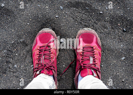 Flat top lay closeup high angle view looking down on black volcanic rocks sand beach in Reynisfjara, Vik, Iceland, with vibrant red sports shoes feet - Stock Photo