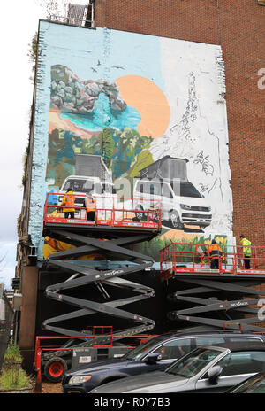 Clerkenwell, London, UK. 7th Nov 2018. Workers dodged the showers on Clerkenwell Road, in central London today, to work on a camper van scene mural, brightening up a car park. Credit: Monica Wells/Alamy Live News Stock Photo