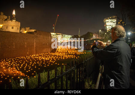 Tower of London, UK. 7th Nov 2018. Visitors pictured viewing the installation at the Tower of London.  As the nation commemorates the centenary of the end of the First World War, a new installation at the Tower of London, Beyond the Deepening Shadow: The Tower Remembers will fill the moat with thousands of individual flames: a public act of remembrance for the lives of the fallen, honouring their sacrifice.   Credit: phil wilkinson/Alamy Live News Stock Photo