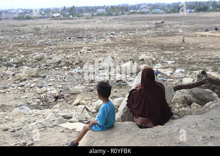 Palu, Central Sulawesi, Indonesia. 1st Nov, 2018. A women and her son are seen seated in the affected area of the tsunami liquefaction in palu.A deadly earthquake measuring 7.5 magnitude and the tsunami wave caused by it has destroyed the city of Palu and much of the area in Central Sulawesi. According to the officials, the death toll from the devastating earthquake and tsunami has risen to 2088, around 5000 people in hospitals are seriously injured and some 62,000 people have been displaced. Credit: Risa Krisadhi/SOPA Images/ZUMA Wire/Alamy Live News - Stock Photo