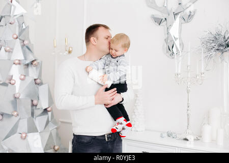 Lovely father keeping son on hands, hugging and kissing him in christmas studio - Stock Photo
