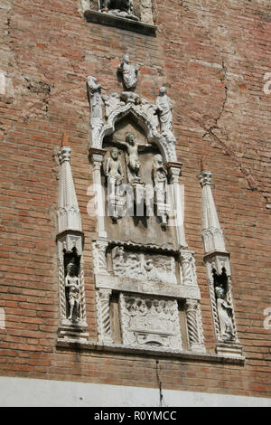 Venice, high relief in marble on a red brick facade - Stock Photo