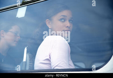 multicultural teenage girl looking out of window of bus - Stock Photo