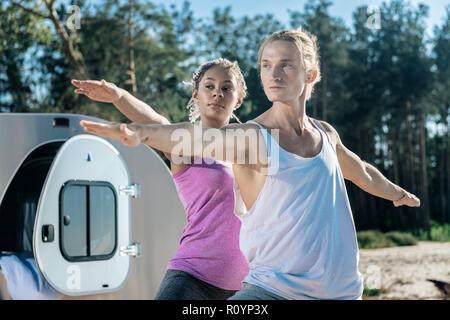 Handsome athletic man doing yoga with his slim girlfriend outside - Stock Photo