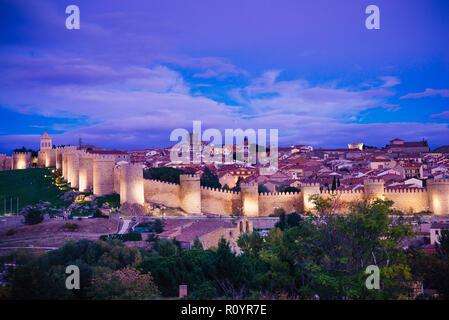 View from Cuatro Postes over the medieval city walls of Avila at dusk. Avila, Castilla y Leon, Spain, Europe