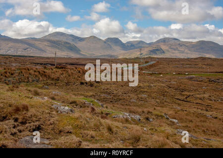 Traffic on a bog road across Ireland with the mountains of Connemra County Galway in background. N59 Leenane to Clifden with peat boglands adjacent. - Stock Photo