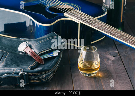 guitar and whiskey on a wooden table, musician relaxed dinner background - Stock Photo