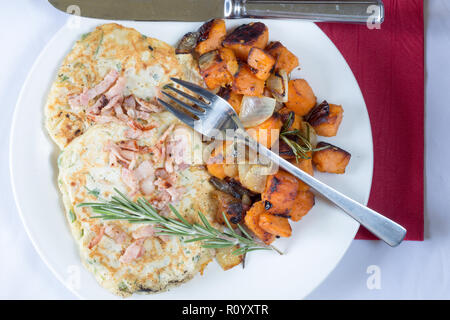 Savoury/savory Cheese and Bacon drop scones served with oven roasted sweet potato and onion. - Stock Photo