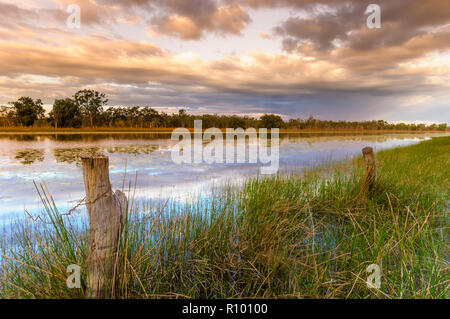 Sunset falls on old fence line posts bordering a large outback waterhole on a cattle station in Cape York, Queensland. - Stock Photo